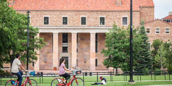 students ride bcycles on Norlin quad