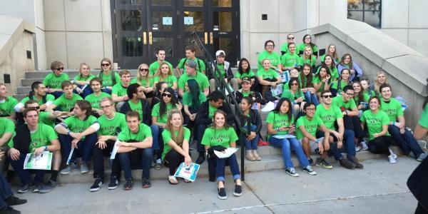 Volunteer Green Stampede members sitting on steps outside building