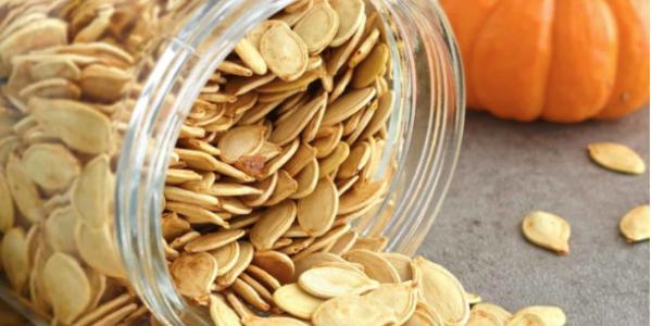 Pumpkin seeds falling out of a jar