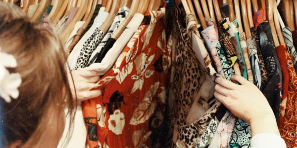 shopper searches through a rack of hanging clothes