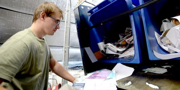 Man sorting two blue bins of recycled material at a facility