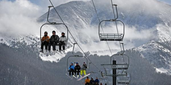 A full 3-person chairlift on a clear winter day