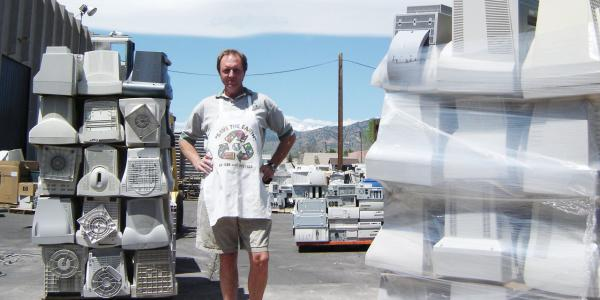 Man standing in front of wrapped computers to be recycled