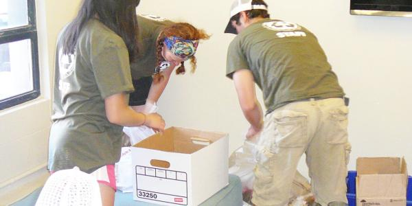three people in green shirts packing a white moving box
