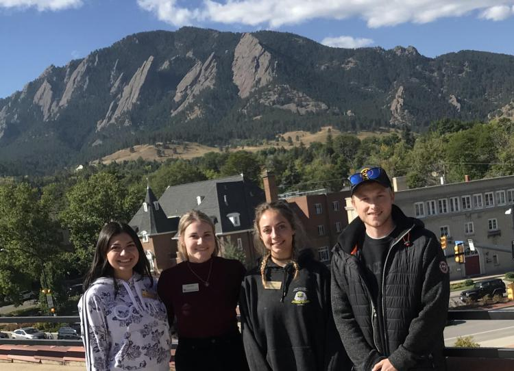 Green Team students smiling in group with Boulder flatirons in background