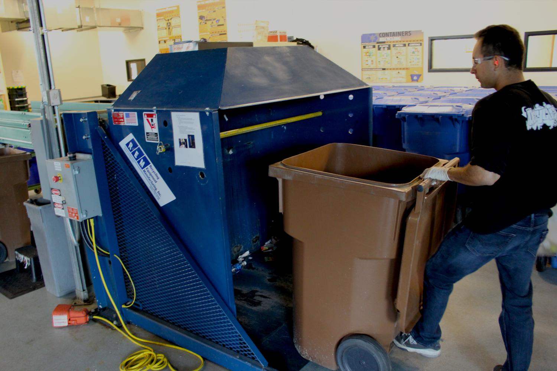 A student worker loads the dumper