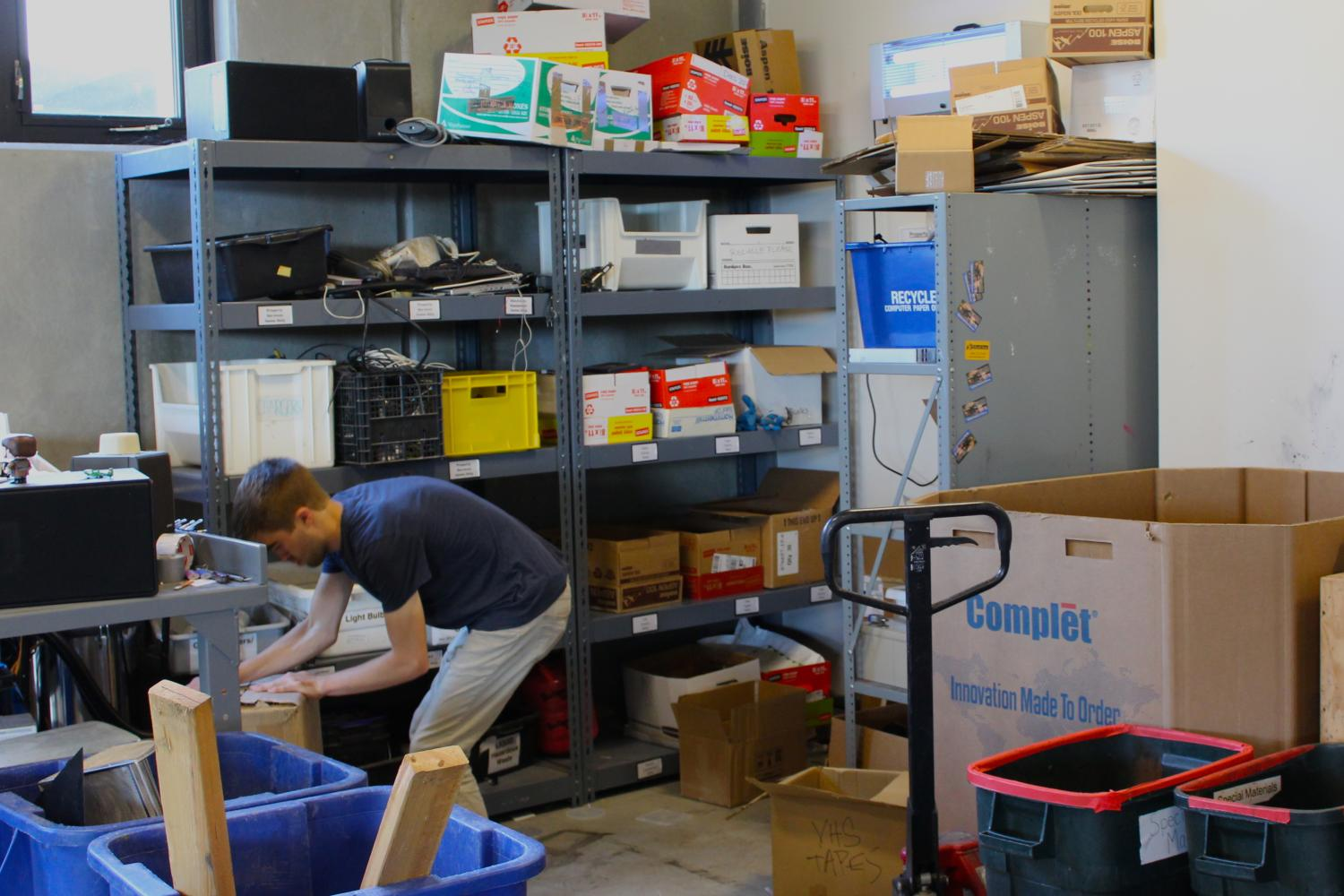 A student worker organizes bins of special materials recycling