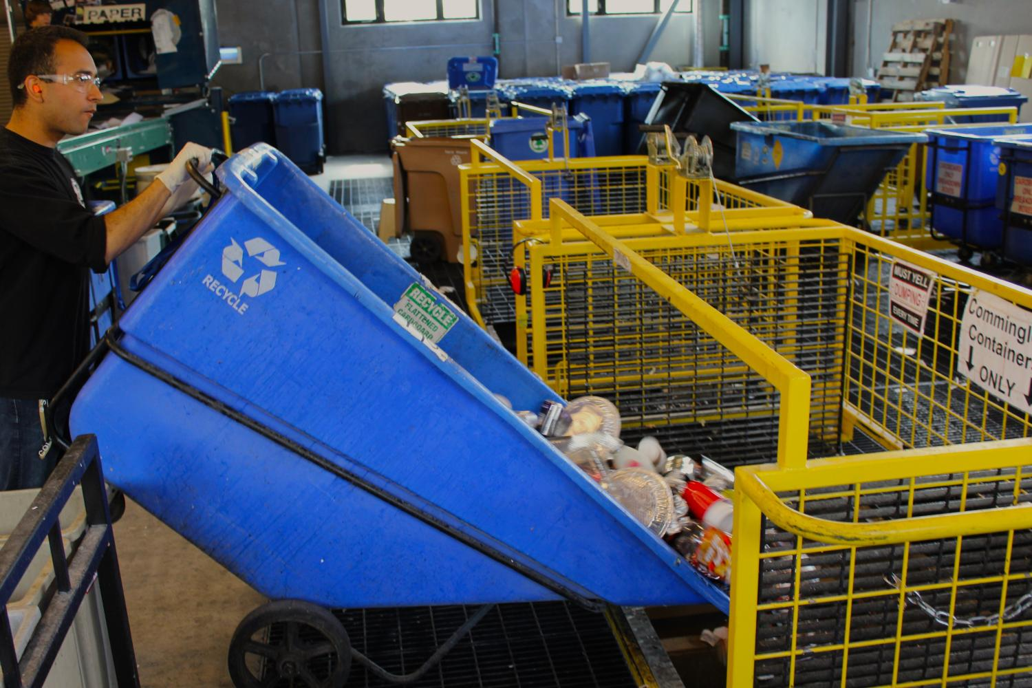 """A student worker dumps the contents of a full tip cart into a """"roll off"""" bin"""