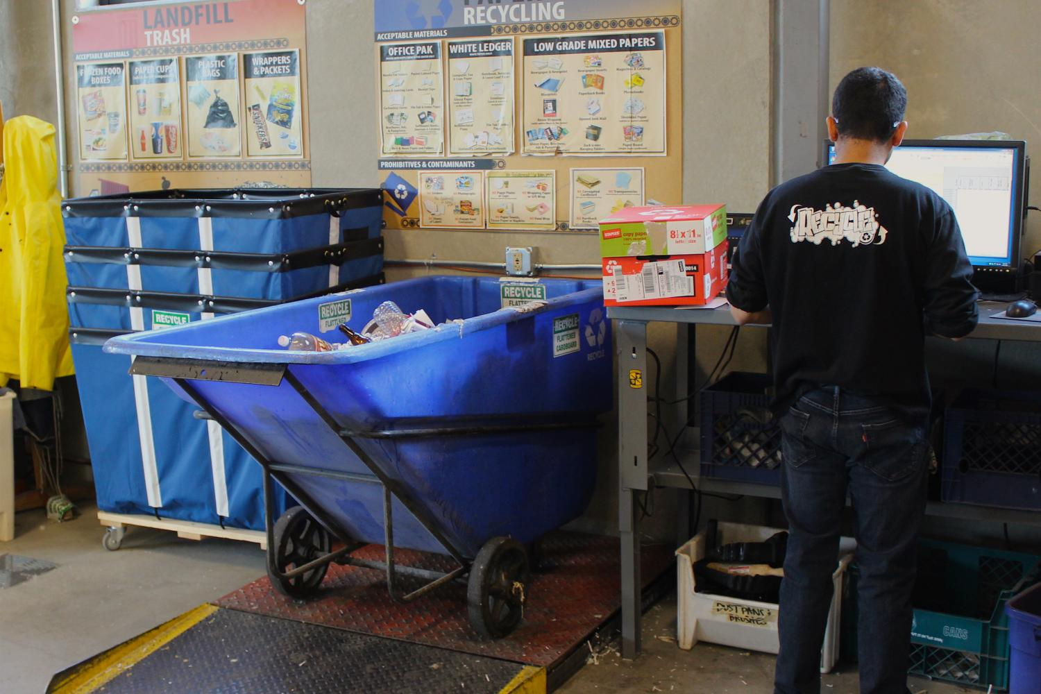 A student worker weighs a full tip cart of recycling