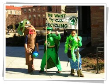 Students in hero costumes holding a recycling banner