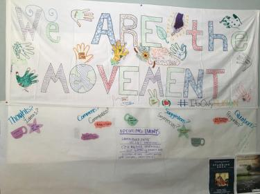 "Photo of banner Eco-Social Justice Leadership Program students created which reads ""We are the Movement"" and has their handprints around it"