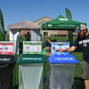 a Ralphie's Green Stampede member uses compost and recycling bins on Franklin Field