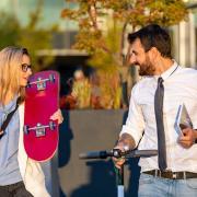 woman with skateboard man with bike