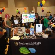 Students stand behind a table covered with Environmental Center promotional posters and giveaway items