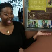 Student in front of food and justice week posters