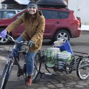 A student rides a bike towing a trailer full of recycling and compost bins for giveaway