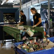 Two students stand sorting at a recycling conveyor belt in the CU recycling facility as cans and bottles roll past them into a large bin