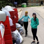 students stand next to bags of donations
