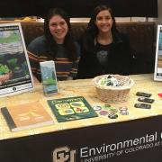 Students at table of promotional items