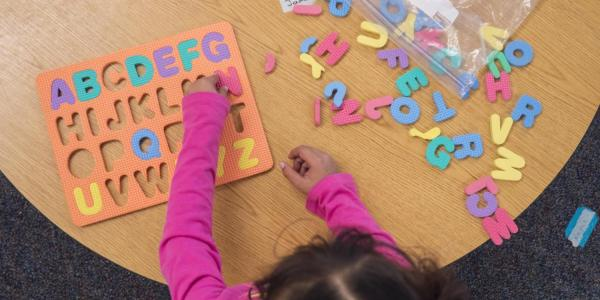Girl with alphabet toy