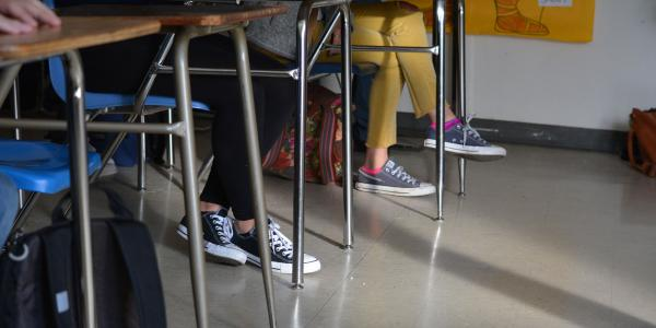 Feet and legs of students sitting at desks in a classroom