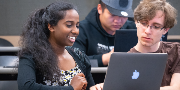two students smiling and reading a computer screen