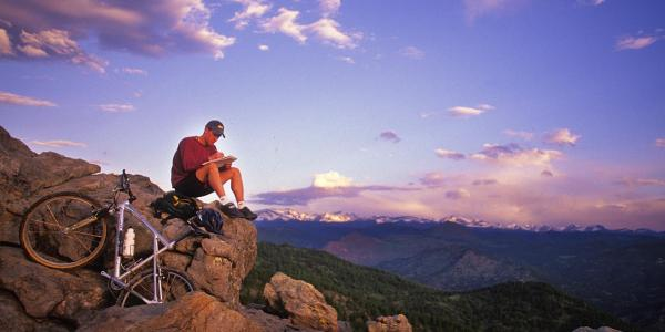 A man sitting on the Flatirons with his mountain bike and journal with the mountains in the background