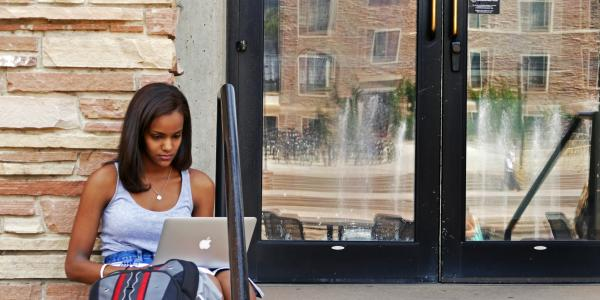 A CU student working on a laptop outside of a university building