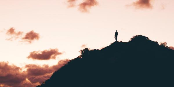 A person at the top of a mountain top at sunset