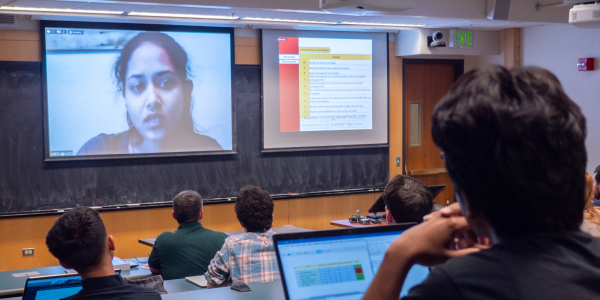 female student on screen and other students in the classroom