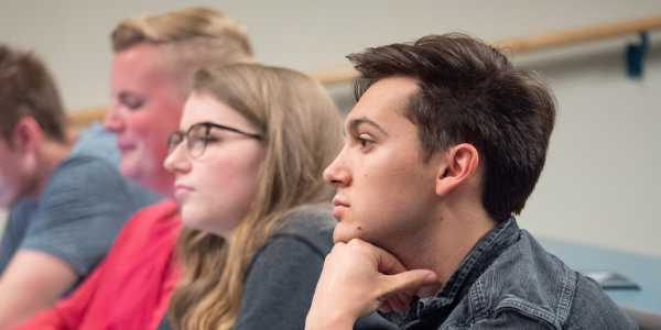 male student, female student looking thoughtful in class