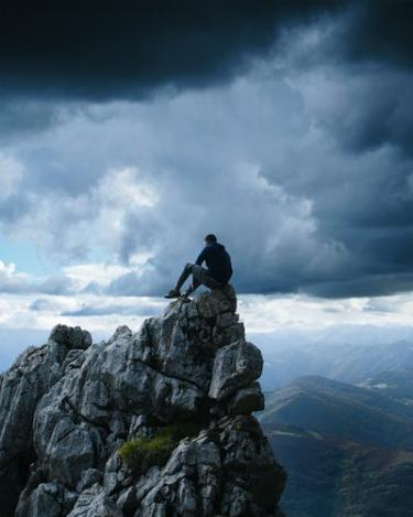 man sitting on top of mountain with stormy sky
