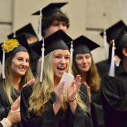 Group of female students in their caps & gowns and clapping at graduation