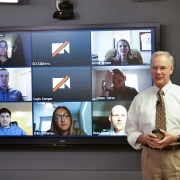 Professor Moorer in front of screen with distance students