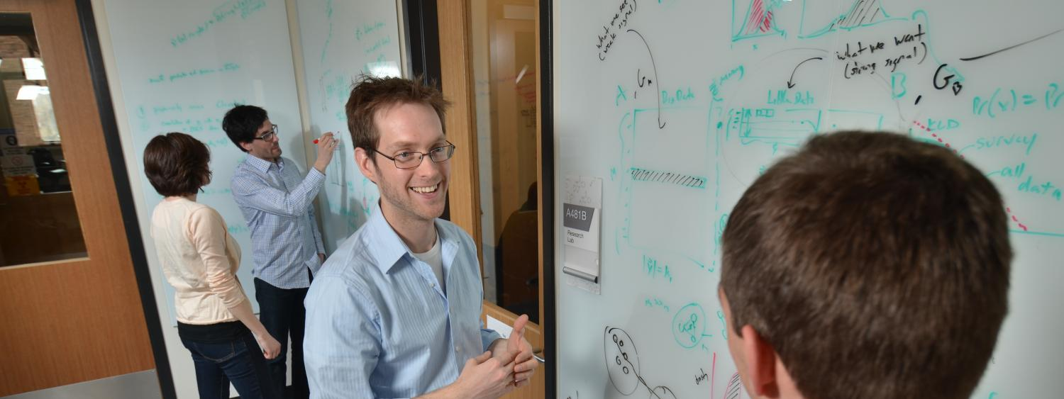 Professor Aaron Clauset teaching a student at the white board