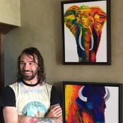Carson Bruns poses with paintings he created