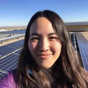 Kyri Baker poses in front of solar panels