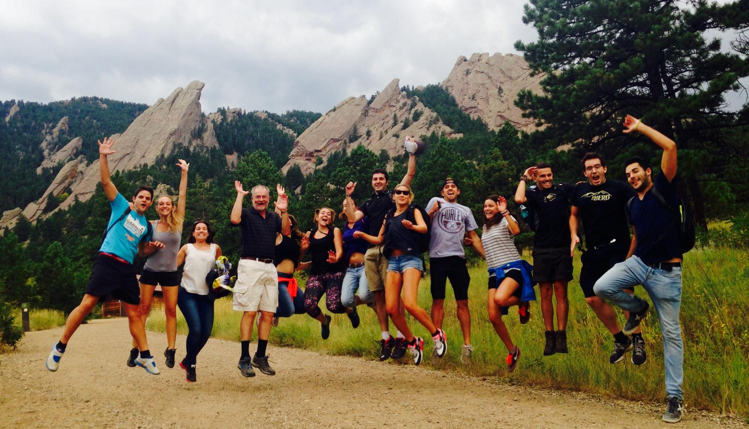 New Balsells Fellows on a welcome hike, jumping, with Flatirons in the background.