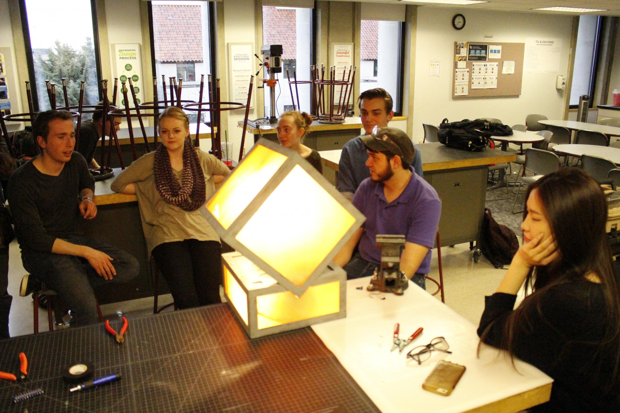 The class illuminates the prototype during a work session.