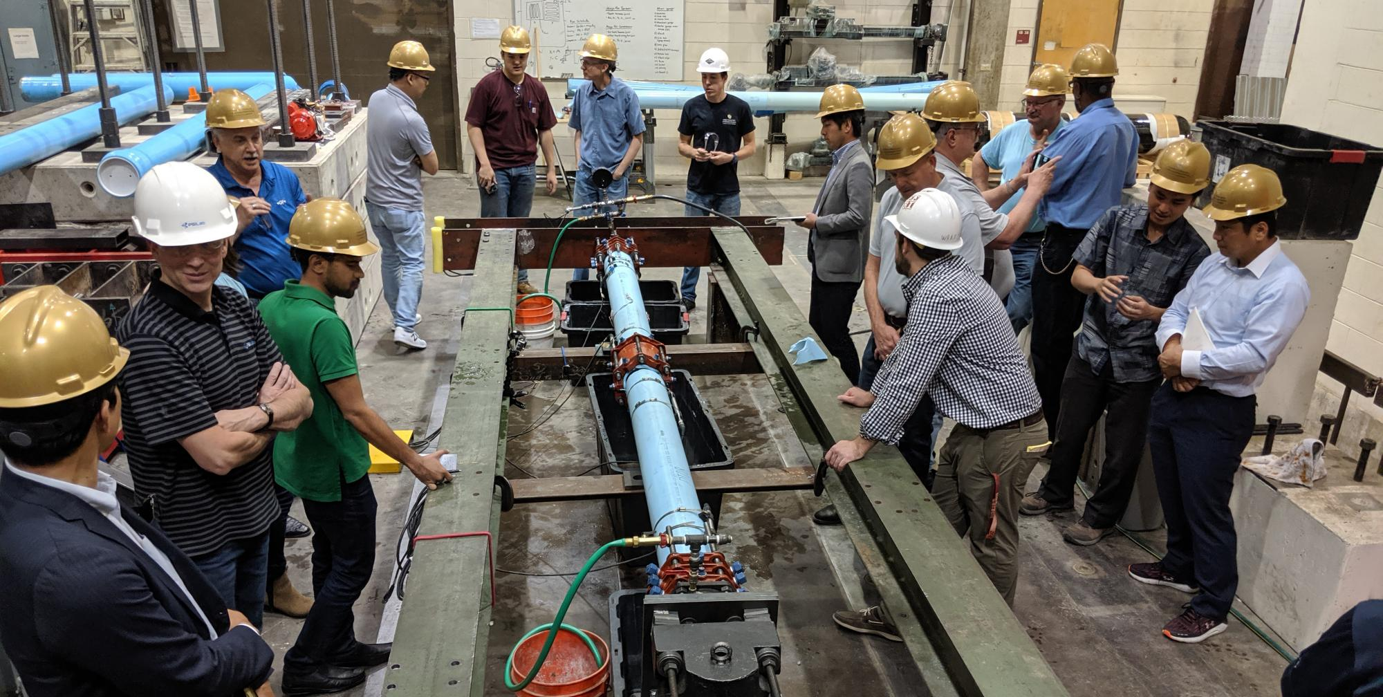 A group of water experts gather around the seismic testing equipment in the CIEST lab.