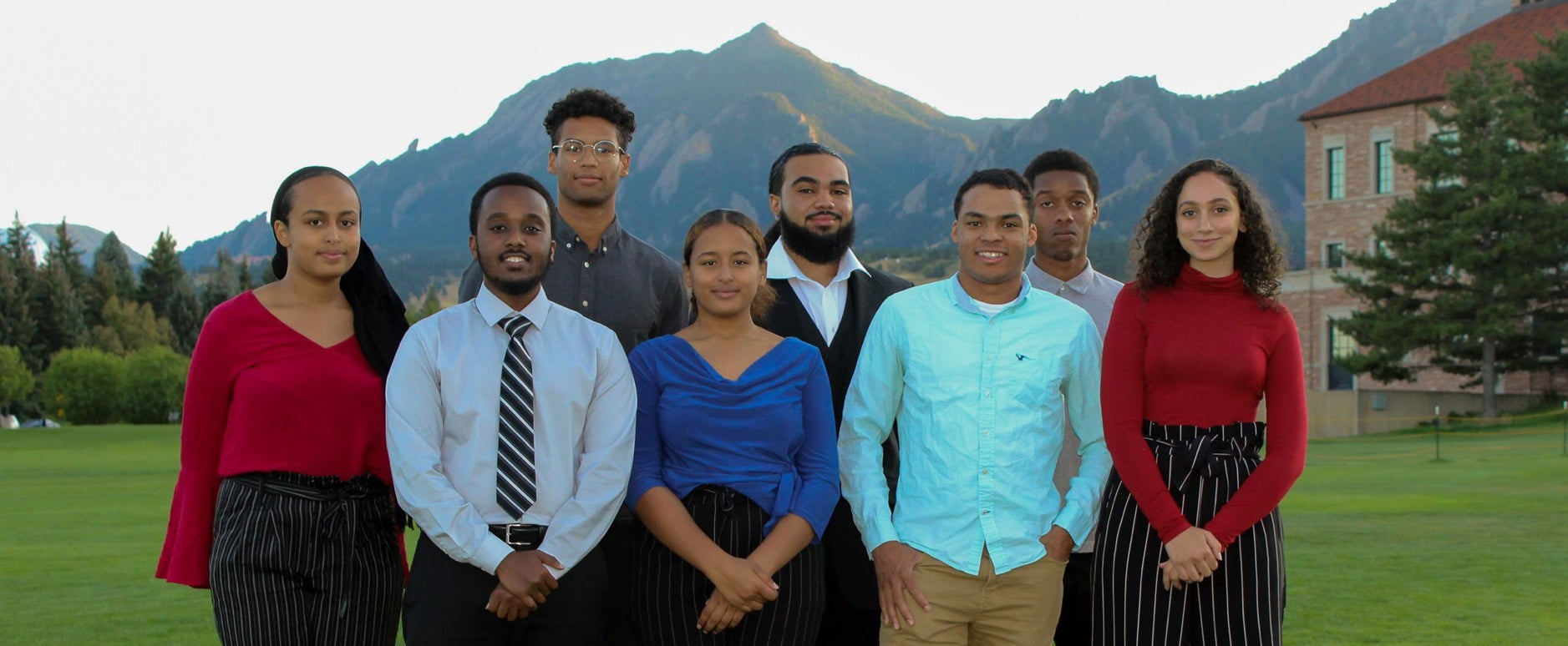 The executive leadership board of the CU Boulder NSBE chapter poses for a group photo on the business field.
