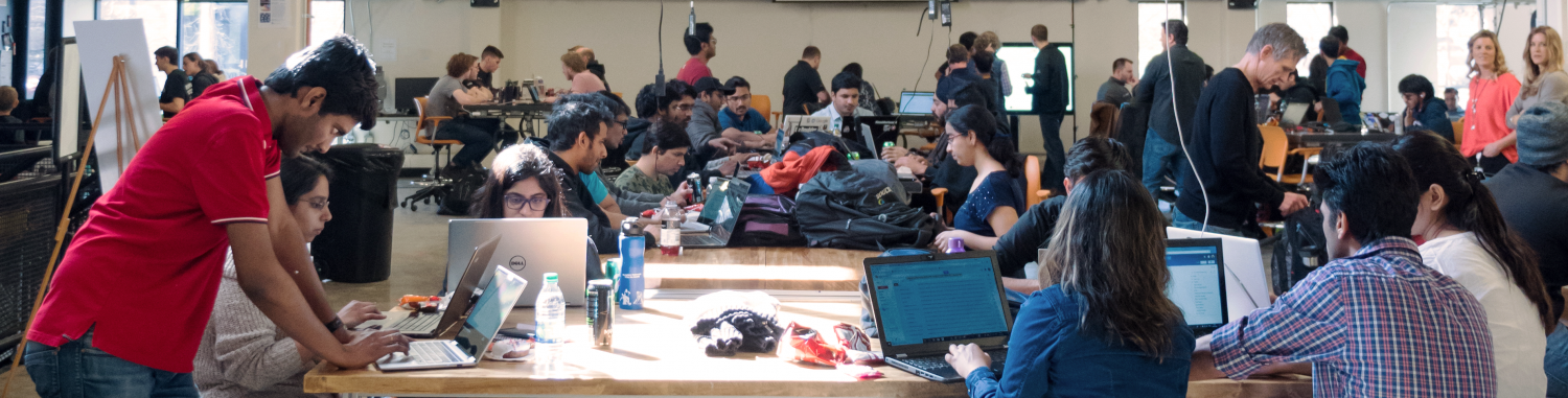 Students in a large room collaborating with each other in front of computers.