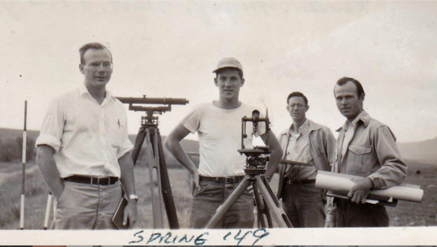 Four students standing with surveying equipment