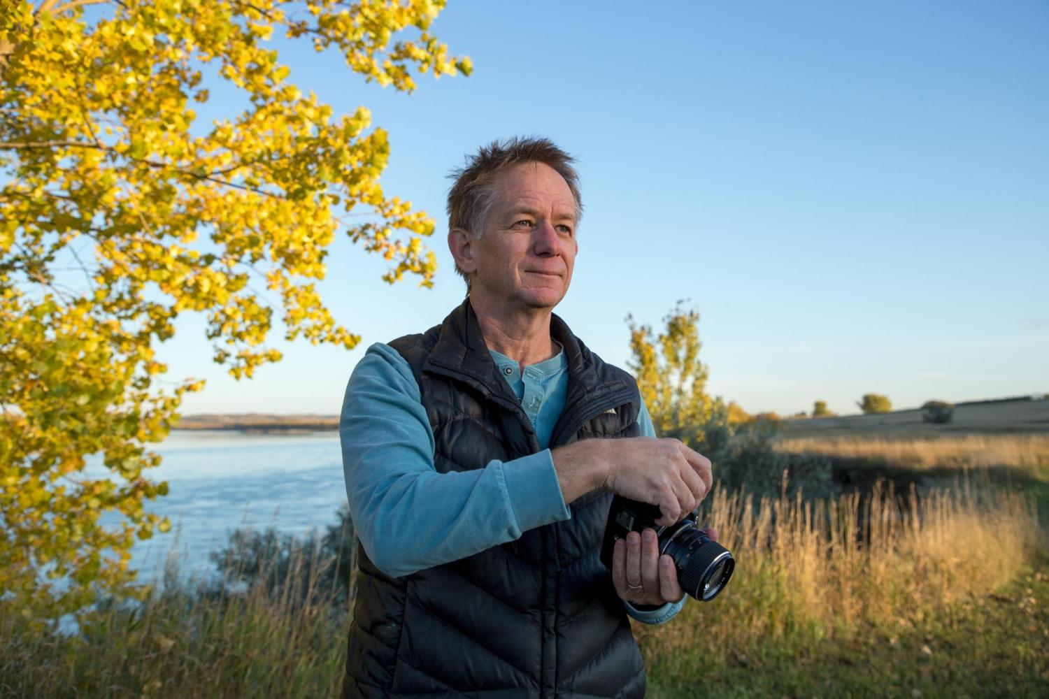 Kent with his camera by a lake with fall trees