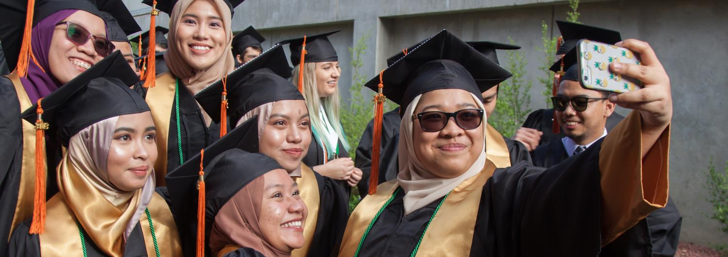 Female students pose for selfie during graduation