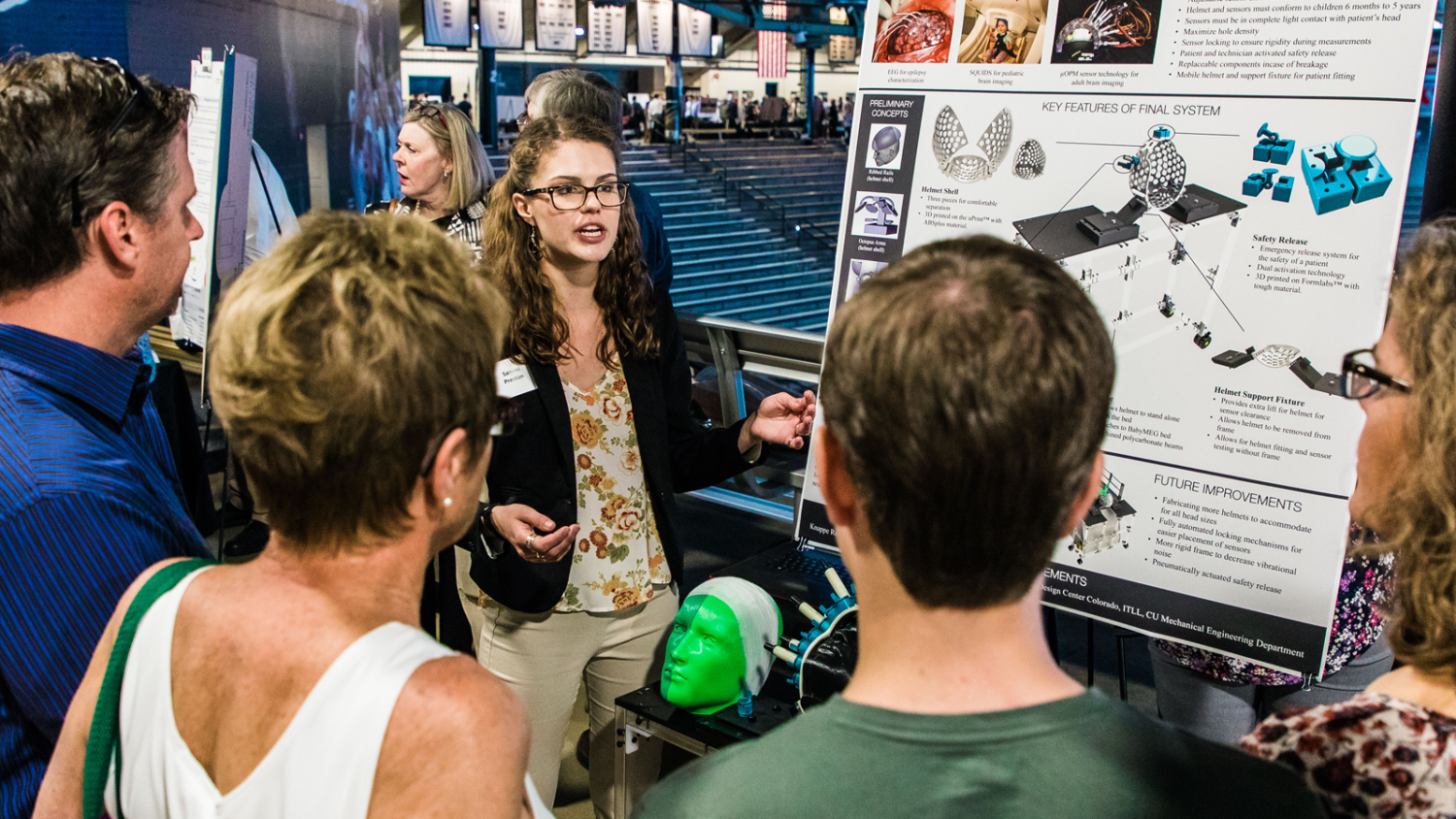 A female student explains her senior project to an audience at the Engineering Projects Expo