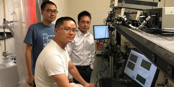 Ronggui Yang in a lab with two students.