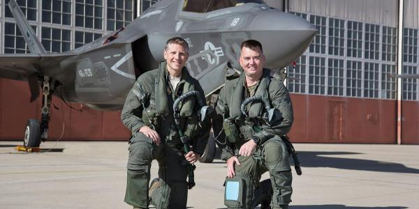 Hamilton and Frey kneel in front of a fighter jet in full flight gear.