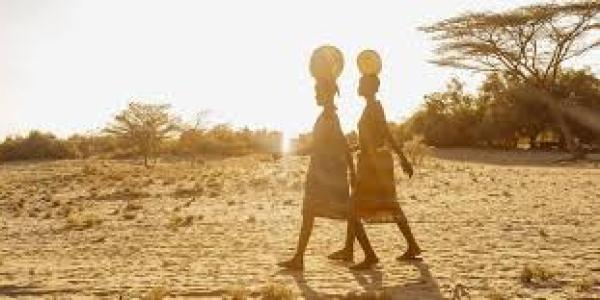 Women walking in Africa with water barrels on their heads