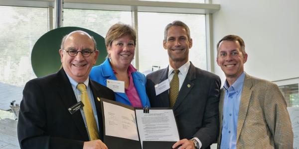 Phil DiStefano, Terri Fiez, Keoki Jackson, and Bobby Braun with the agreement.